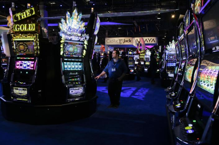 Jeffery Uss of Casino Inc., stops to play various slot machines at the Global Gaming Expo, Wednesday, Sept. 25, 2013, in Las Vegas. As slot machines move away from moving parts to video technology, manufacturers are now rolling out the first generation of joystick-controlled, penny arcade-themed gambling machines. (AP Photo/Julie Jacobson)