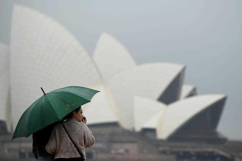A woman shelters from the rain in front of the Sydney Opera House during wet weather at Circular Quay.