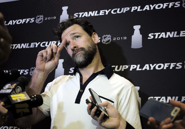 FILE - In this Wednesday, May 8, 2019, file photo, Carolina Hurricanes' Justin Williams talks with reporters during an NHL hockey media availability in Boston. Paying the bills, going out to dinner and cutting the grass can fall by the wayside for NHL players on long playoff runs. Williams loses track of what day it is: Its either a game day or not a game day, though doing a daily newspaper crossword puzzle reminds him that its actually, say, Saturday. (AP Photo/Steven Senne, File)