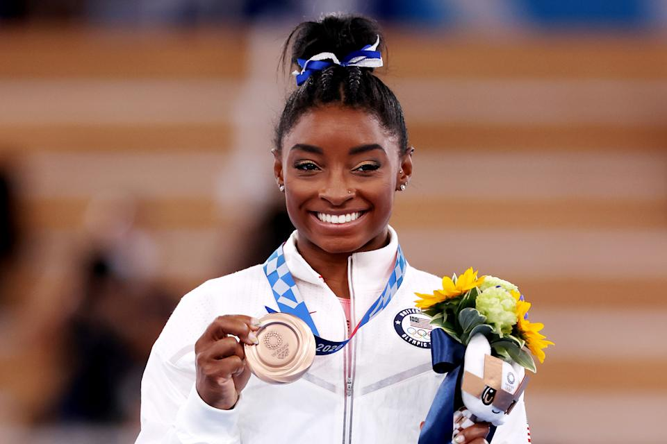 Simone Biles shows off her bronze medal at the Tokyo Olympics.