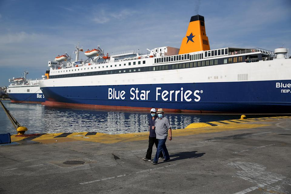 People walk next to a moored passenger ferry during a 24-hour general strike at the port of Piraeus
