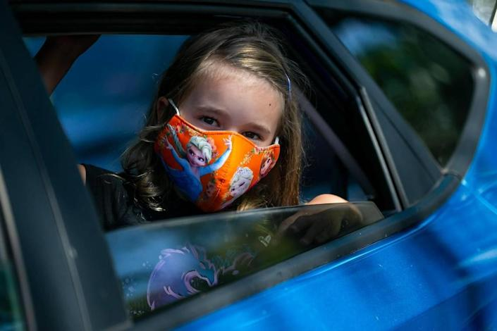 Lily Sherwood, 5, attends a drive-thru distribution event at Joseph C. Carter Park in Fort Lauderdale, Florida on Saturday, Aug. 8, 2020. Volunteers distributed food, sanitation items, backpacks and back-to-school necessities during the Eighth Annual Sunshine Health Orange Bowl Family, Fun & Fit Day drive-thru only event.