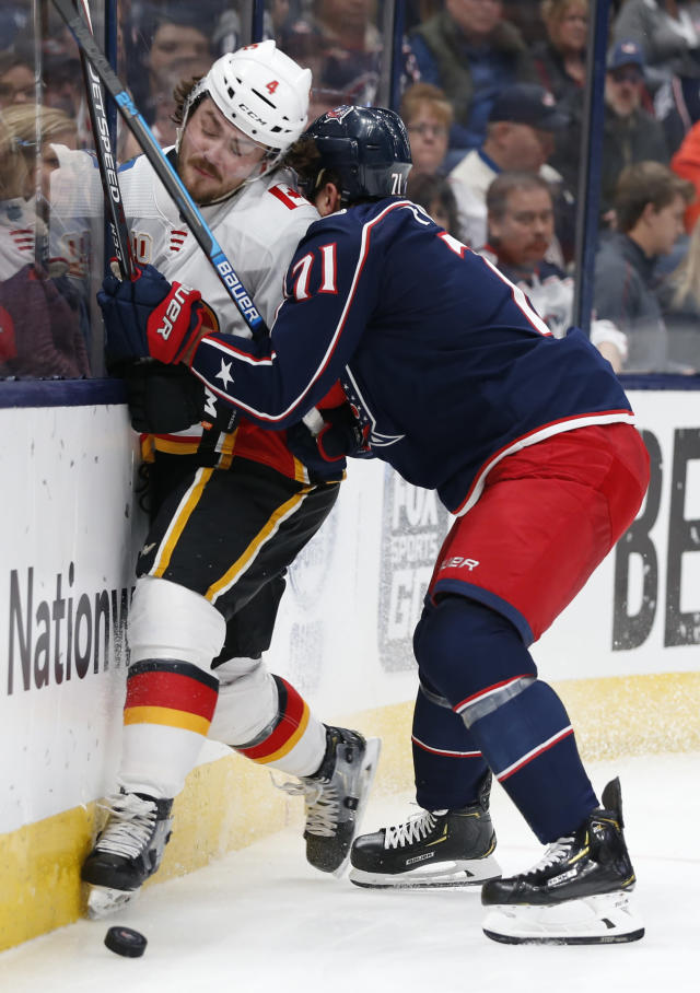 Columbus Blue Jackets' Nick Foligno, right, checks Calgary Flames' Rasmus Andersson, of Sweden, during the second period of an NHL hockey game Saturday, Nov. 2, 2019, in Columbus, Ohio. (AP Photo/Jay LaPrete)