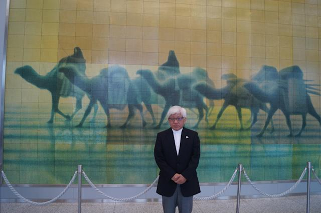 "<p>Kenji Shiga, the director of the Hiroshima Peace Memorial Museum, stands in front of ""€œCaravan of Peace: East (Sun)."" The mosaic featured in the museum is based on a drawing by atomic-bomb survivor Ikuo Hirayama. (Photo: Michael Walsh/Yahoo News) </p>"