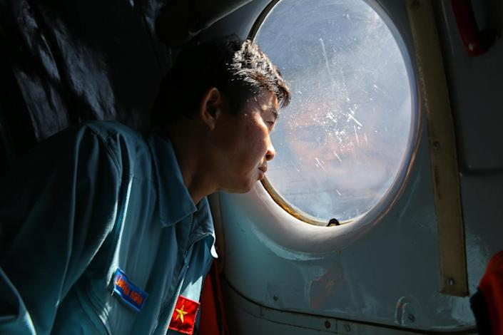 Officer Lang Van Ngan of the Vietnam Air Force looks out the window onboard a flying AN-26 Soviet made aircraft during a search operation for the missing Malaysia Airlines flight MH370 plane over the southern sea between Vietnam and Malaysia Friday, March 14, 2014. Vietnam says it has downgraded but not stopped its search for the missing jetliner in the South China Sea and has been asked by Malaysian authorities to consider sending planes and ships to the Strait of Malacca. (AP Photo/Na Son Nguyen)