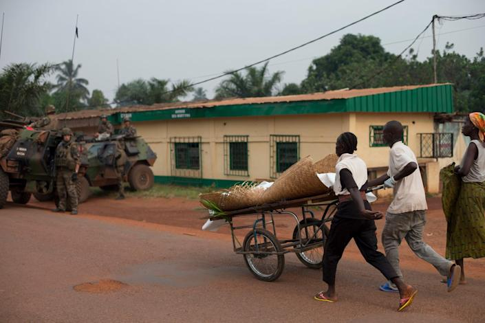 A family pushes home the body of an 18-year-old boy, killed by stray gunfire, in the Miskine neighborhood of Bangui, Central African Republic, Thursday, Dec. 26, 2013. The spokesman for an African Union peacekeeping force says six Chadian peacekeepers were killed and 15 were wounded, after being attacked Wednesday.(AP Photo/Rebecca Blackwell)