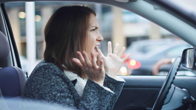 Angry woman driving her car experiencing road rage