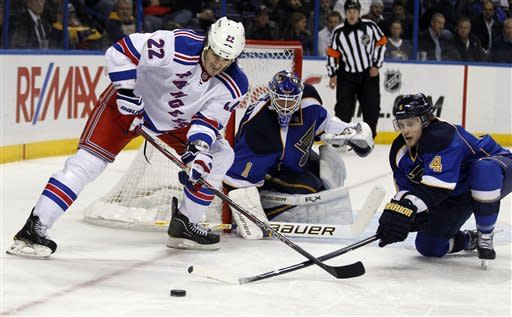 New York Rangers' Brian Boyle, left, tries to reach a loose puck as St. Louis Blues goalie Brian Elliott, center, and Kris Russell defend during the third period of an NHL hockey game Thursday, Dec. 15, 2011, in St. Louis. The Blues won 4-1. (AP Photo/Jeff Roberson)