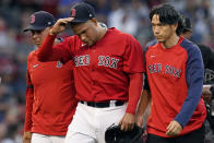Boston Red Sox starting pitcher Eduardo Rodriguez, leaves with an injury, accompanied by manager Alex Cora, left, and team trainer Masai Takahashi iduring the second inning of the team's baseball game against the New York Yankees at Fenway Park, Friday, July 23, 2021, in Boston. (AP Photo/Elise Amendola)