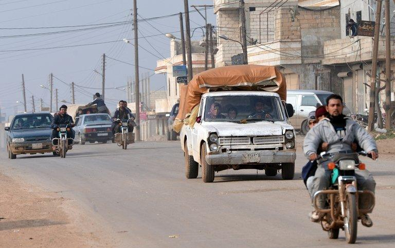 Syrian residents flee the fighting in Kurnaz, close to the western city of Hama, on January 27, 2013