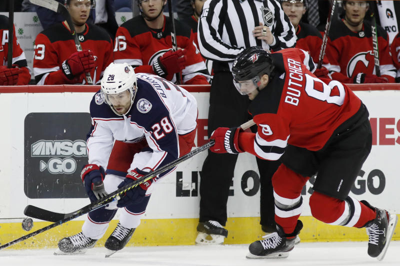 New Jersey Devils defenseman Will Butcher (8) defends against Columbus Blue Jackets right wing Oliver Bjorkstrand (28) during the first period of an NHL hockey game Sunday, Feb. 16, 2020, in Newark, N.J. (AP Photo/Kathy Willens)
