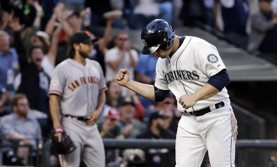 Seattle Mariners' Mike Zunino, right, pumps his fist after scoring as San Francisco Giants starting pitcher Madison Bumgarner walks behind after backing up the play at home in the sixth inning of a baseball game Wednesday, June 17, 2015, in Seattle. (AP Photo/Elaine Thompson)
