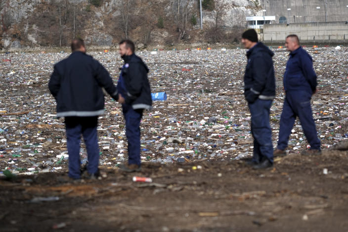 Workers look at garbage floating in the Drina river near Visegrad, eastern Bosnia, Wednesday, Feb. 24, 2021. Environmental activists in Bosnia are warning that tons of garbage floating down the Balkan country's rivers are endangering the local ecosystem and people's health. The Drina River has been covered for weeks with trash that has piled up faster than the authorities can clear it out. (AP Photo/Kemal Softic)