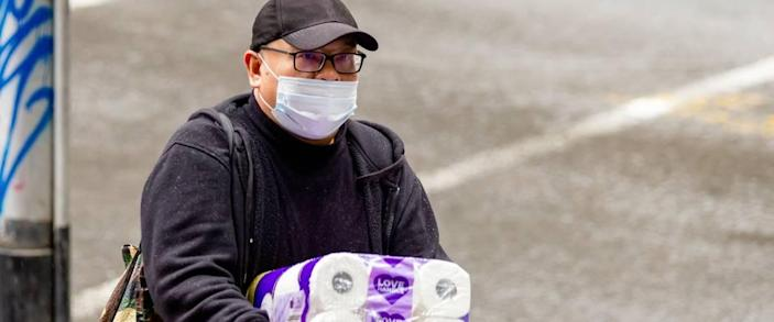 man wearing face mask walks with large case of paper towels