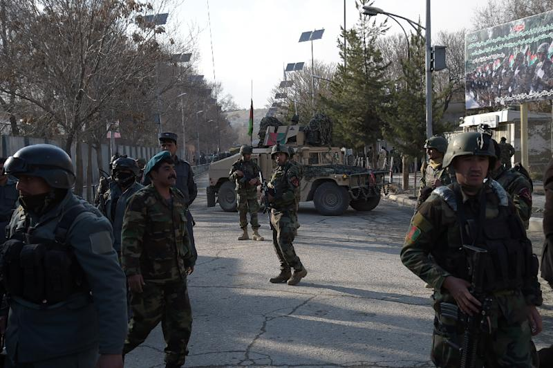 Afghan security personnel stand guard in front of the main gate of a military hospital in Kabul on March 8, 2017, after a deadly attack claimed by the Islamic State group
