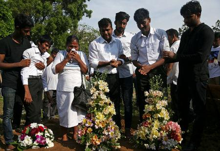 People react during a mass burial of victims, two days after a string of suicide bomb attacks on churches and luxury hotels across the island on Easter Sunday, at a cemetery near St. Sebastian Church in Negombo, Sri Lanka April 23, 2019.   REUTERS/Athit Perawongmetha
