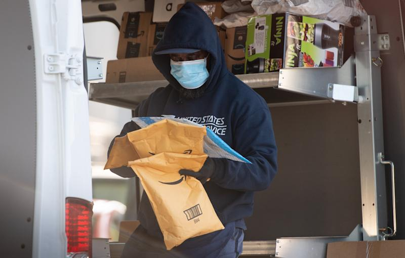 A mailman wearing a mask and gloves to protect himself and others from COVID-19, known as coronavirus, loads a postal truck with packages at a United States Postal Service (USPS) post office location in Washington, DC, April 16, 2020. - For many Americans, checking the mailbox is a daily ritual, a constant in a quickly changing world that can yield anything from wedding invitations to tax audits to new clothes. But as with many ordinary things as the coronavirus crisis unfolds, the US Postal Service -- already compromised by a mountain of debt -- has a most uncertain future. (Photo by SAUL LOEB / AFP) (Photo by SAUL LOEB/AFP via Getty Images)