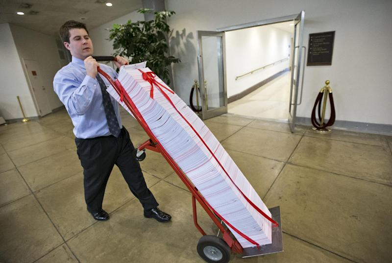 "A Senate aide delivers a stack of documents bound in red tape being used as a prop during debate on the budget in the Senate, at the Capitol in Washington, Friday, March 22, 2013. The paperwork was described as the federal regulations dealing with the Affordable Care Act, often called ""Obamacare."" (AP Photo/J. Scott Applewhite)"