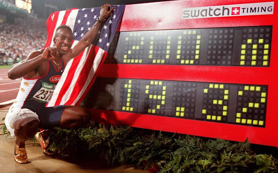 ATLANTA, GA - AUGUST 1:  Michael Johnson of the US (L)  poses for the press next to the clock after the men's Olympic 400m race at the Olympic Stadium in Atlanta, Georgia, 01 Aug. Johnson hurtled into history books in world record time as he completed an unprecedented Olympic double with the 400m and the 200m. Johnson clocked 19.32 sec to destroy Frankie Fredericks of Namibia (19.68) and Ato Boldon of Trinidad (19.80). (FOR EDITORIAL USE ONLY) AFP-IOPP/ Eric FEFERBERG  (Photo credit should read AFP-IOP/AFP via Getty Images)