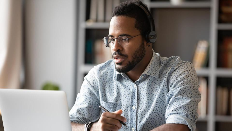 Focused young african businessman wear headphones study online watching webinar podcast on laptop listening learning education course conference calling make notes sit at work desk, elearning concept.