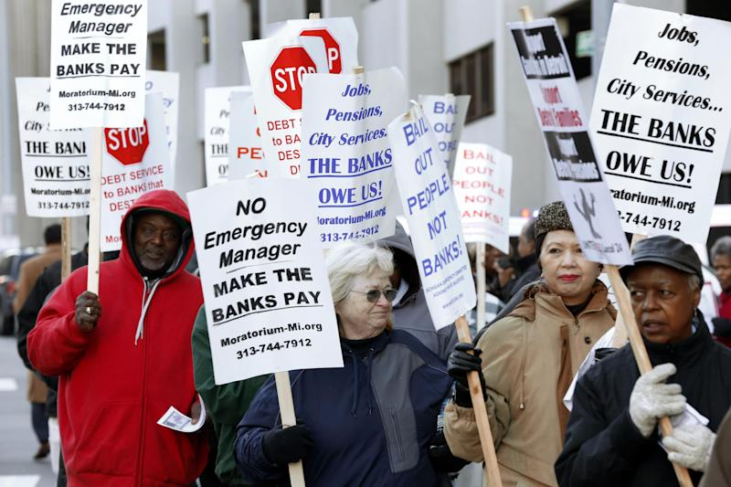 FILE - In this Oct. 23, 2013 file photo protesters rally outside federal court during Detroit's bankruptcy proceedings. Judge Steven Rhodes, who is overseeing the case, found the city eligible to remake itself under Chapter 9 on Dec. 3 and also declared that pensions aren't immune to cuts in a final plan. Rhodes said Monday, Dec. 16, 2013 that the decision can immediately be appealed to a higher court and he is thinking about whether he'll recommend that a federal appeals court put the case on a fast track. (AP Photo/Paul Sancya, File)