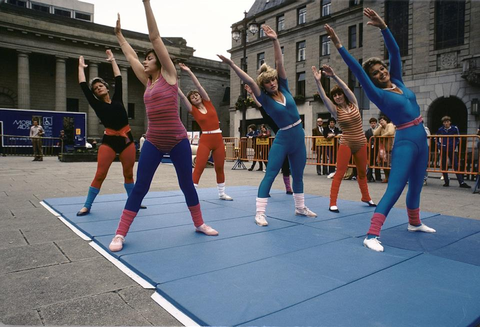 Group of women doing aerobics exercise class outdoors in leotards in city square 1983