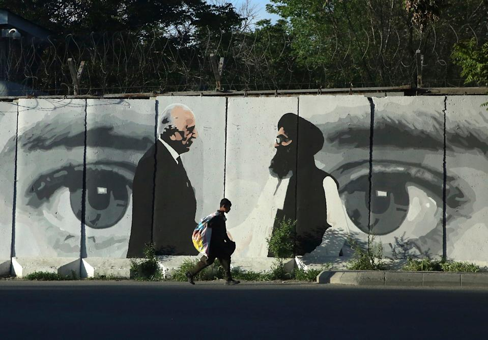 Graffiti in Kabul depicts US peace envoy Zalmay Khalilzad, left, and Mullah Abdul Ghani Baradar, Taliban representativeAP