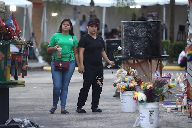 <p>Natascha Soto and Melinda Vargas (L-R) visit the memorial setup outside the Pulse gay nightclub as they remember those lost one year ago during a mass shooting on June 12, 2017 in Orlando, Florida. (Joe Raedle/Getty Images) </p>