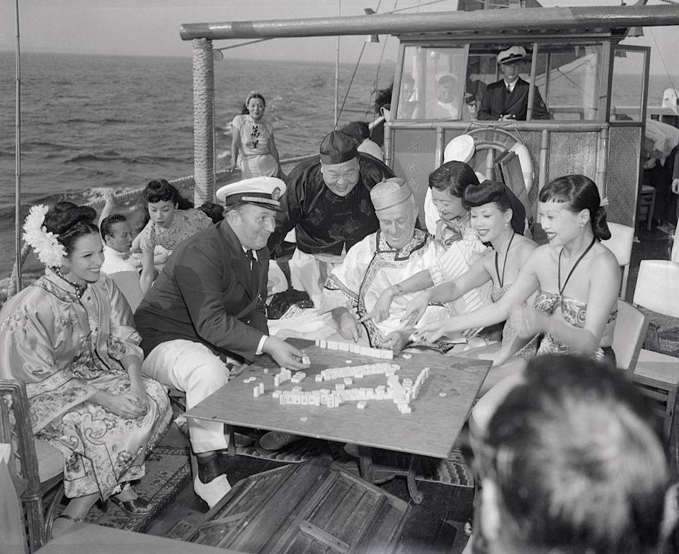 """Robert L. Ripley (seated, in captain's hat) and various guests enjoy a game of mah-jongg aboard the Mon Lei, a junk (type of Chinese sailing ship) he brought across the Pacific from Kowloon, on a cruise on the Long Island Sound in Aug. 1946. Ripley was known for his eponymous show """"Believe it or Not!"""" which featured """"unusual"""" facts from around the world.<span class=""""copyright"""">Bettmann Archive—Getty Images</span>"""