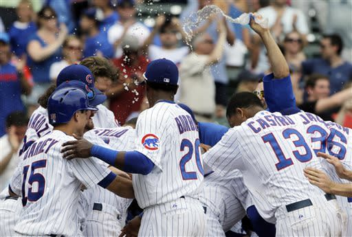 Chicago Cubs' Dioner Navarro (obscured) celebrates with teammates after hitting a sacrifice fly during the 11th inning of a baseball game against the Pittsburgh Pirates in Chicago, Sunday, July 7, 2013. The Cubs won 4-3. (AP Photo/Nam Y. Huh)