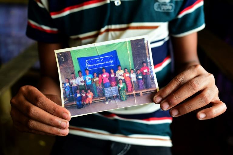 Young Rohingya refugee Mohammad Ayaz shares a creased family photo photograph, grainy and faded -- one of the few possessions he managed to keep hold of after fleeing Myanmar