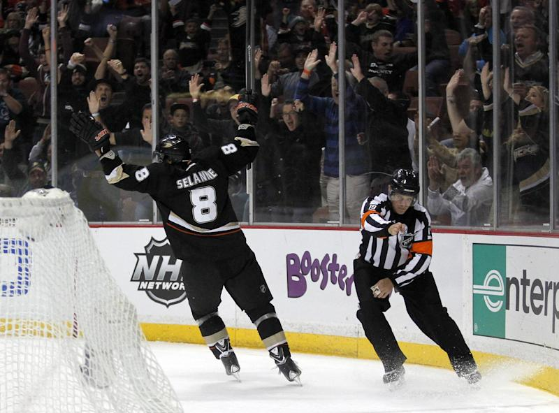 Anaheim Ducks right wing Teemu Selanne (8), of Finland, celebrates scoring a goal against the Calgary Flames as referee Gord Dwyer, making the call, during the second period of an NHL hockey game, Wednesday, Oct. 16, 2013, in Anaheim, Calif. (AP Photo/Alex Gallardo)