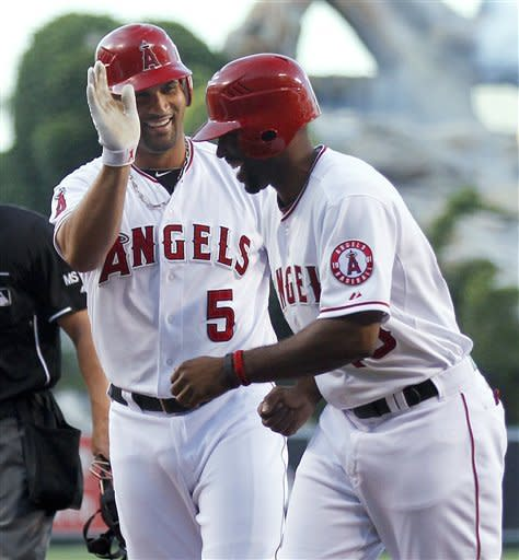 Los Angeles Angels' Albert Pujols celebrates his three-run home run with Torii Hunter against the San Francisco Giants during the first inning of a baseball game in Anaheim, Calif., Tuesday, June 19, 2012. (AP Photo/Chris Carlson)