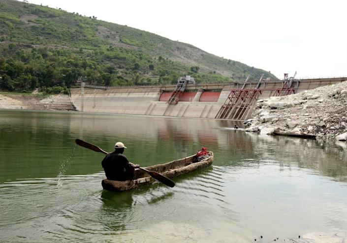 In this file photo from April 20, 2010, a man passes by the Peligre dam in central Haiti, which supplies electricity.