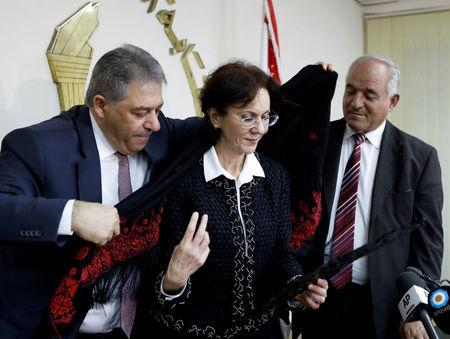 Palestinian Ambassador to Lebanon Ashraf Dabbour (L) helps U.N. Under-Secretary General and ESCWA Executive Secretary Rima Khalaf (C) put on a traditional Palestinian scarf after a news conference announcing her resignation from the United Nations in Beirut, Lebanon, March 17, 2017. REUTERS/Jamal Saidi