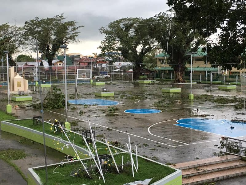 Fallen tree branches litter a basketball court after Typhoon Phanfone swept through Tanauan, Leyte, in the Philippines