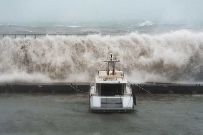 TOPSHOT - Big waves overpass a breakwater at the Port Olympic marina in Barcelona as storm Gloria batters Spanish eastern coast on January 21, 2020. - Freezing winds, heavy snow and rain lashed parts of Spain yesterday, killing three people, forcing the closure of schools that cancelled classes for nearly 200,000 students and disrupting travel, officials said. (Photo by Josep LAGO / AFP) (Photo by JOSEP LAGO/AFP via Getty Images)
