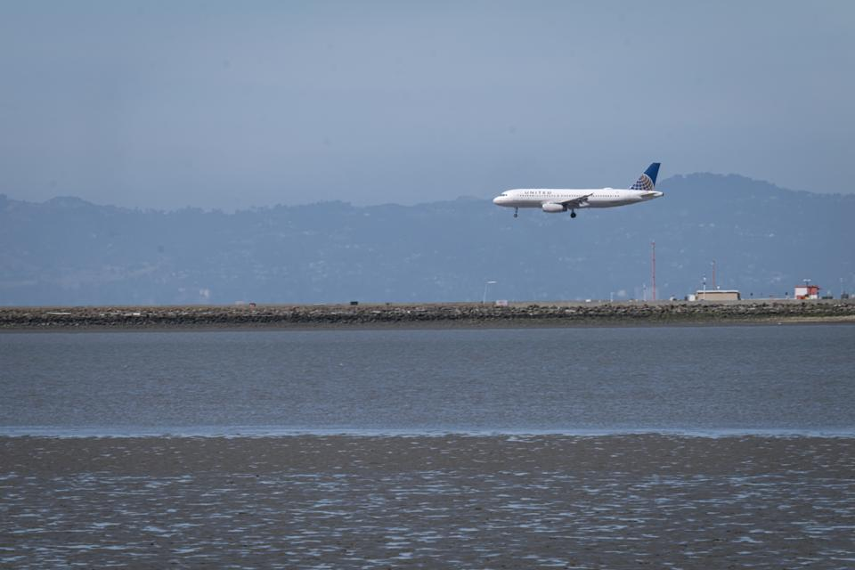 A passenger aircraft, operated by United Airlines Holdings Inc., prepares to land at San Francisco International Airport (SFO) in San Francisco, California, U.S., on Monday, June 1, 2020. U.S. airlines have yet to tap $29 billion in federal pandemic relief loans as they wait to see whether the reopening of the economy revives demand and diminishes the need for money that comes with government strings attached. (David Paul Morris/Bloomberg via Getty Images)