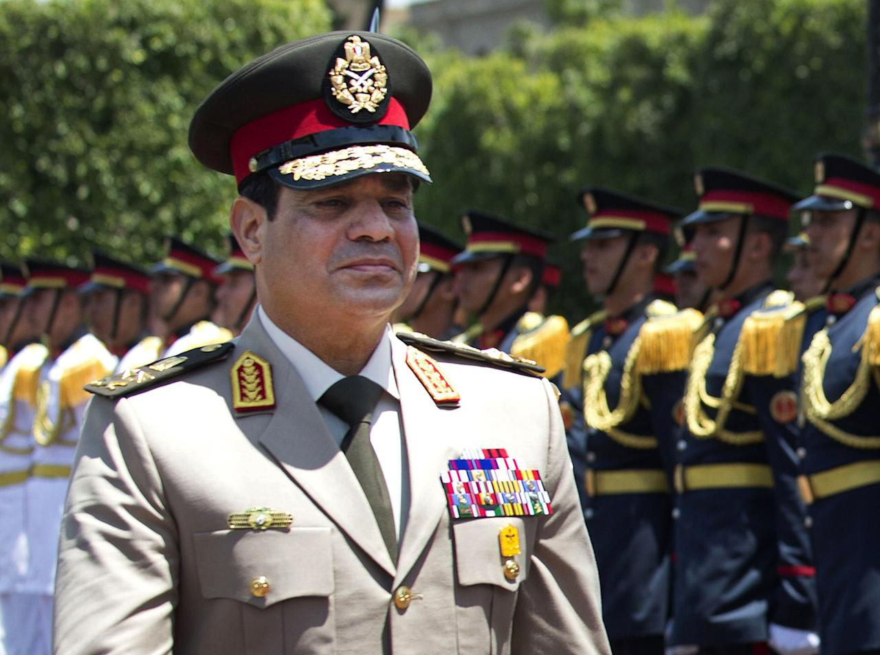 "FILE - In this Wednesday, April 24, 2013 file photo, Egyptian Defense Minister Gen. Abdel-Fattah el-Sissi reviews honor guards during an arrival ceremony for his U.S. counterpart at the Ministry of Defense in Cairo. Egypt's military chief says he ""can't turn his back"" if the majority of Egyptians want him to run for president. El-Sissi's comments, made in a speech Tuesday, March 4, 2014 to military cadets and reported by the state news agency MEAN, are his strongest yet suggesting he intends to run. (AP Photo/Jim Watson, Pool, File)"