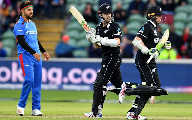 Afghanistan's Aftab Alam looks on as New Zealand's Kane Williamson and Tom Latham take a quick single - AFP