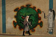 A Palestinian woman, wearing a protective mask amid the COVID-19 pandemic, walks past a coronavirus-inspired mural in Gaza City