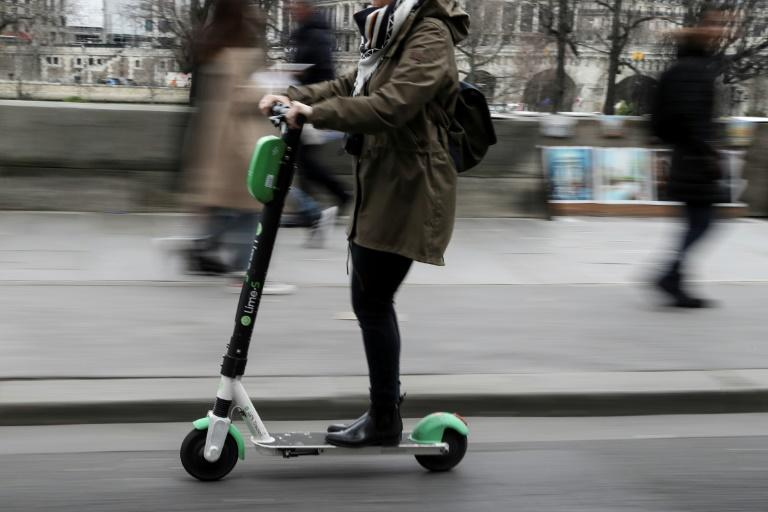 A woman uses an electric scooter of the US company in Paris - but the short lifespan of the vehicles is proving a big issue (AFP Photo/KENZO TRIBOUILLARD)