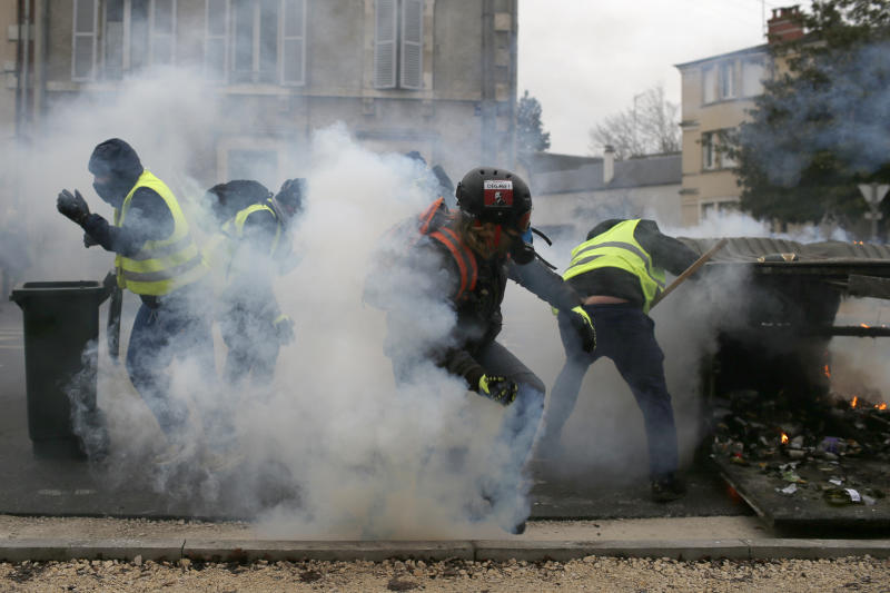 French police fires tear gas as yellow vest demonstrators set up barricades in Bourges, central France, Saturday, Jan. 12, 2019. Paris brought in armored vehicles and the central French city of Bourges shuttered shops to brace for new yellow vest protests. The movement is seeking new arenas and new momentum for its weekly demonstrations. Authorities deployed 80,000 security forces nationwide for a ninth straight weekend of anti-government protests. (AP Photo/Rafael Yaghobzadeh)