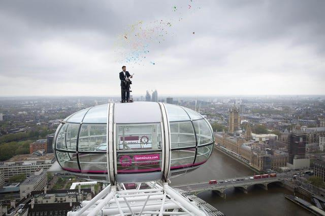 Sunny Jouhal, general manager of the lastminute.com London Eye, stands on top of a London Eye Pod, 135 meters high above the ground to celebrate the re-opening of the attraction (Matt Alexander/PA)