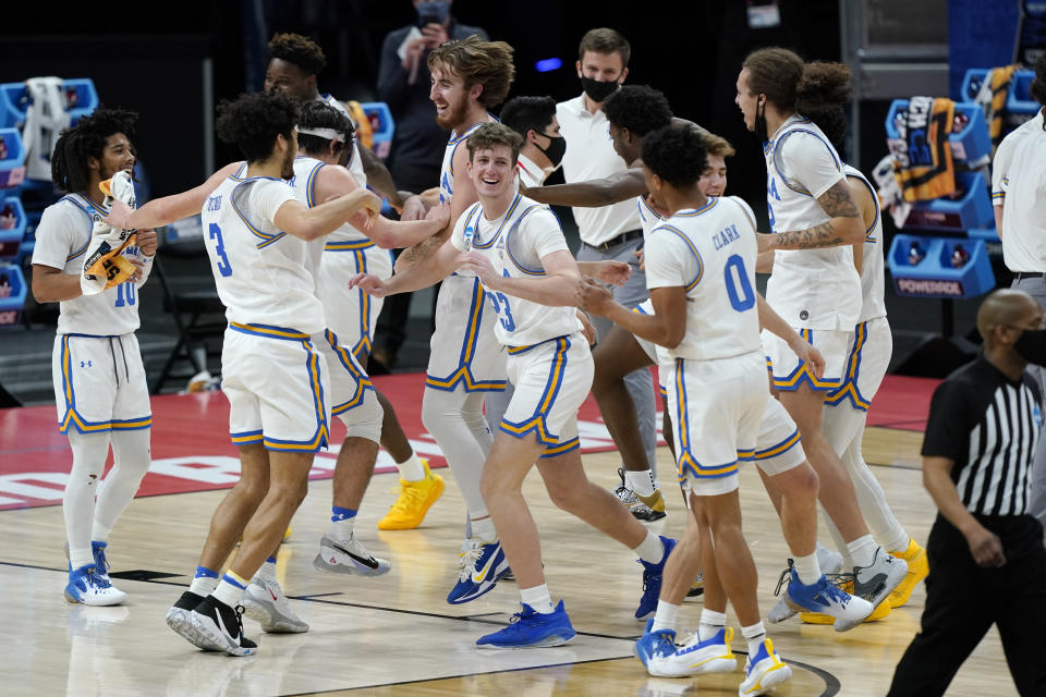 UCLA players celebrate their win over Abilene Christian in a college basketball game in the second round of the NCAA tournament at Bankers Life Fieldhouse in Indianapolis Monday, March 22, 2021. (AP Photo/Mark Humphrey)
