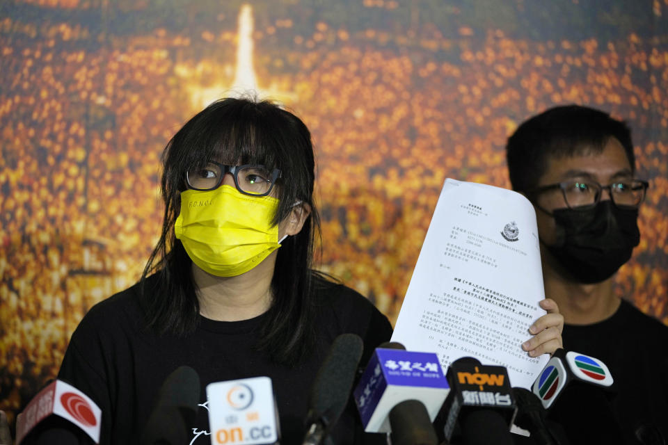 Chow Han Tung, vice chairwoman of the Hong Kong Alliance in Support of Patriotic Democratic Movements of China, shows a document from the police department during a news conference in Hong Kong, Sunday, Sept. 5, 2021. The group behind the annual Tiananmen Square memorial vigil in Hong Kong said Sunday it will not cooperate with police conducting a national security investigation into the group's activities, calling it an abuse of power. (AP Photo/Kin Cheung)