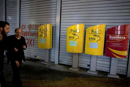 People make their way past mailboxes outside a closed Hellenic Post branch in Athens