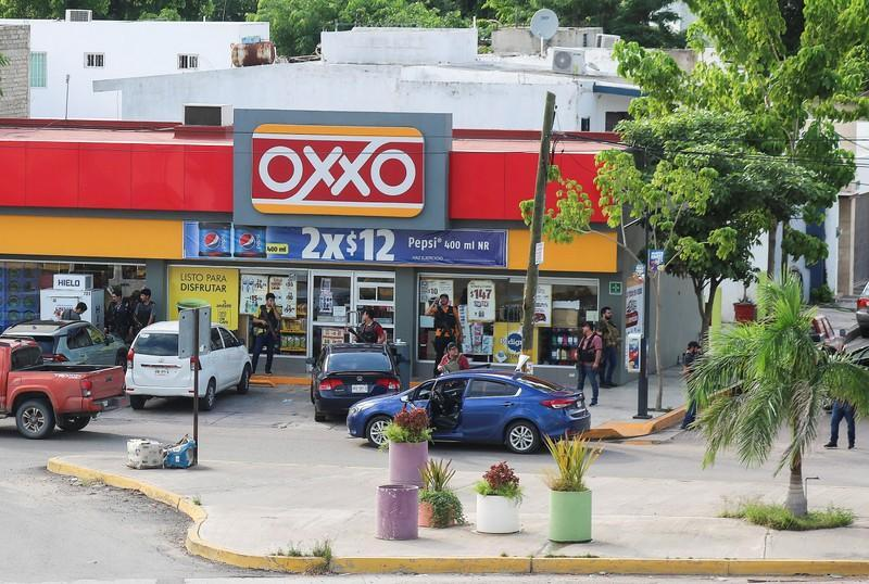 """Cartel gunmen stand outside a store during clashes with federal forces following the detention of Ovidio Guzman, son of drug kingpin Joaquin """"El Chapo"""" Guzman, in Culiacan"""
