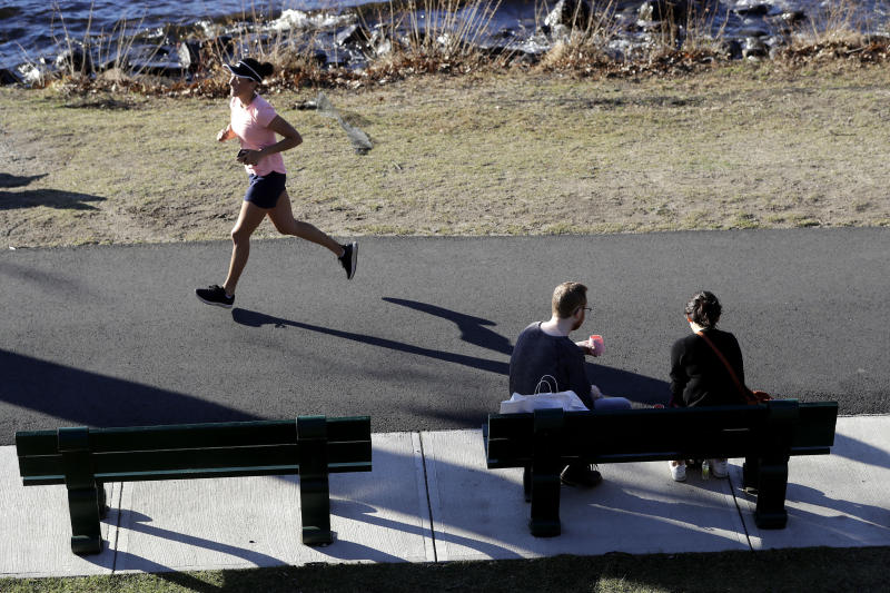A runner makes her way along a path near the Charles River in the Charles River Esplanade park, in Boston, Sunday, Jan. 12, 2020, during unseasonably warm weather. Temperatures climbed into the low 70s in many places in the state Sunday. (AP Photo/Steven Senne)