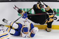 Boston Bruins right wing Chris Wagner (14) is upended by Buffalo Sabres defenseman Jacob Bryson (78) during the first period of an NHL hockey game Tuesday, April 13, 2021, in Boston. (AP Photo/Charles Krupa)